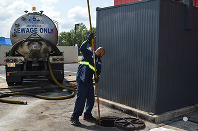 worker performing grease trap pumping