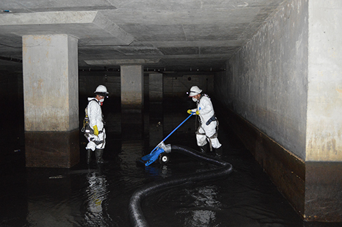 workers performing pump chamber cleaning