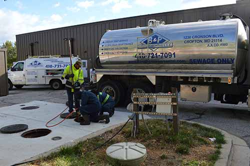 workers performing drain cleaning services